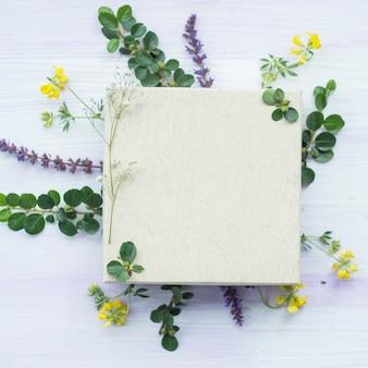 Moldura em branco branca de madeira sob as flores e folhas no plano de fundo texturizado