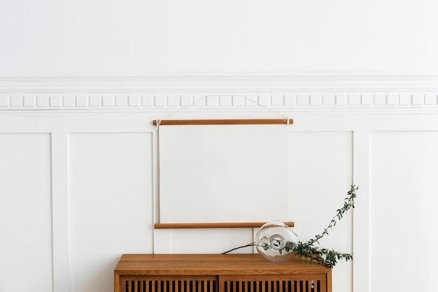 Moldura em branco pendurada acima de um armário de madeira