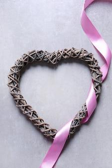 Moldura em forma de coração e fita rosa