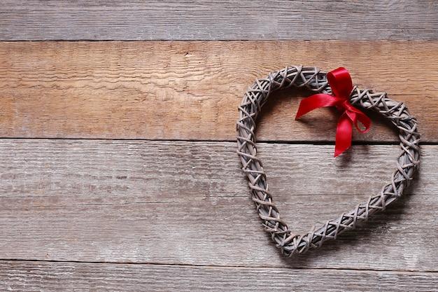 Moldura em forma de coração e fita vermelha
