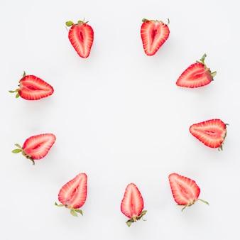 Moldura feita com morangos cortados ao meio em círculo sobre fundo branco