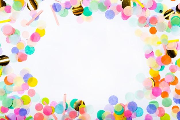 Moldura feita de confetes coloridos sobre fundo branco. cor de fundo de festa com espaço para sua cópia. postura plana. vista do topo