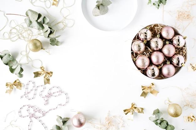 Moldura feita de decoração de natal com bolas de vidro de natal, enfeites, arco, eucalipto.