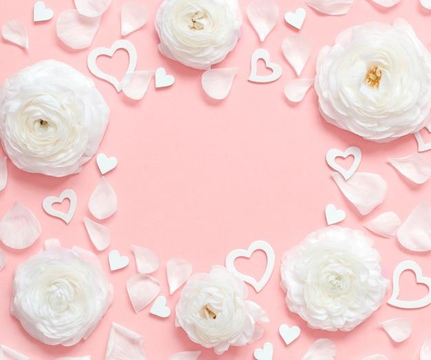 Moldura feita de flores creme, pétalas e corações em uma vista superior rosa claro