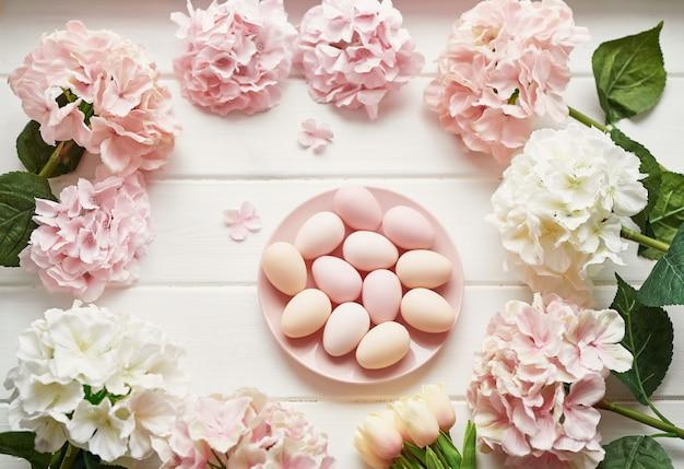 Moldura feita de flores de hortênsia rosa e bege, ovos cor de rosa e tulipas amarelas