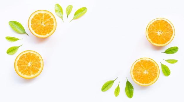 Moldura feita de fruta laranja fresca com folhas verdes sobre fundo branco