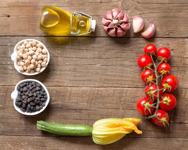 Moldura feita de grão de bico em tigelas com legumes e azeite de oliva em uma mesa de madeira com vista superior do espaço de cópia
