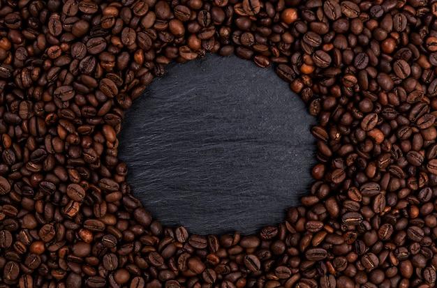 Moldura feita de grãos de café torrados na mesa preta, vista superior