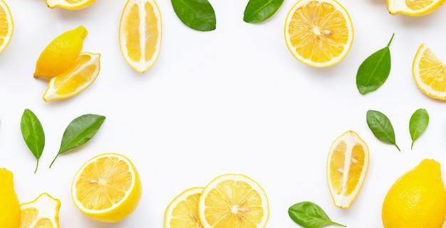 Moldura feita de limão fresco e fatias com folhas isoladas no branco