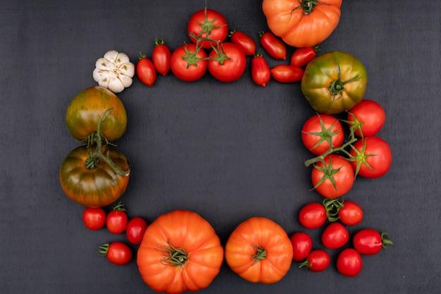 Moldura feita de tomate tomate cereja e alho vista superior na superfície preta