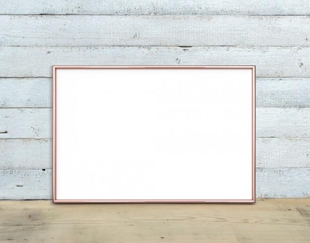 Moldura horizontal em ouro rosa a4 fica em uma mesa de madeira