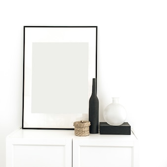 Moldura na cômoda com decoração na parede branca
