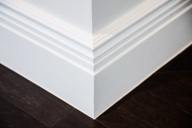 Moldura ornamental no canto de uma sala branca com conceito de interior de assoalho de madeira escura
