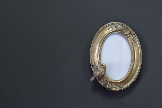 Moldura oval vintage ouro vazia em estilo vitoriano em uma parede cinza, plano de fundo ou conceito