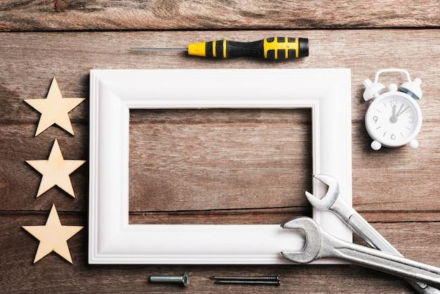 Moldura para fotos com chaves, estrelas e despertador na mesa de madeira, superfície plana