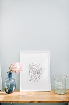 Moldura para fotos com citação caligráfica onde há luz há esperança, flor protea em um vaso em frente à parede azul pastel.