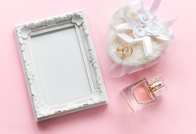 Moldura para fotos e anéis de ouro em um frasco de perfume branco para o aniversário de casamento