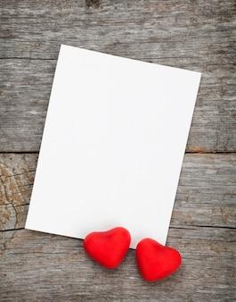 Moldura para fotos e pequenos corações de bombom vermelho em fundo de madeira