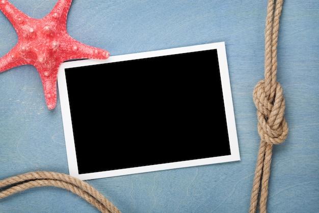 Moldura para fotos em branco com estrela do mar e corda de navio sobre fundo azul de madeira