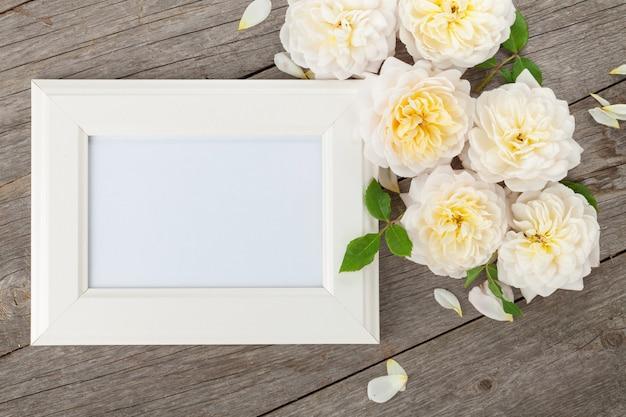 Moldura para fotos em branco e rosas brancas sobre fundo de mesa de madeira