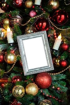 Moldura para fotos em branco vazia em um fundo decorado de natal com brinquedos e velas