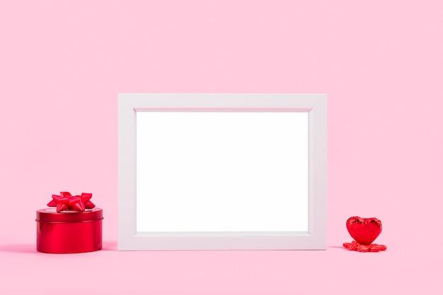 Moldura para fotos entre caixa de presente vermelha e coração de ornamento