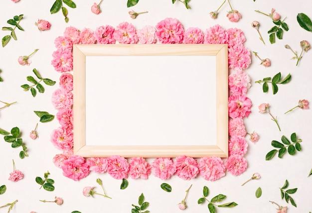Moldura para fotos entre conjunto de flores cor de rosa e folhas verdes