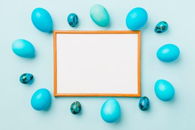 Moldura para fotos entre o conjunto azul de ovos de páscoa