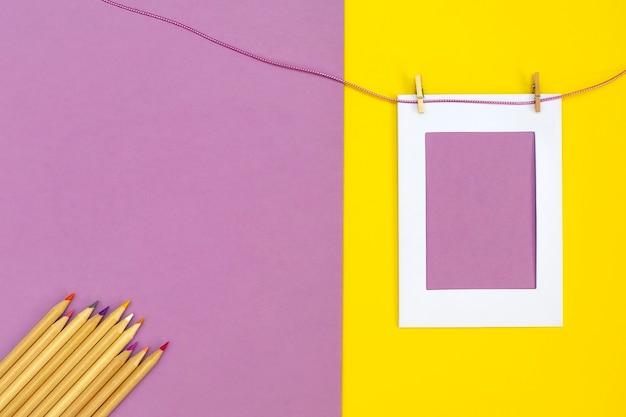 Moldura para fotos vazia em fundo rosa e amarelo com lápis de cor e espaço de cópia
