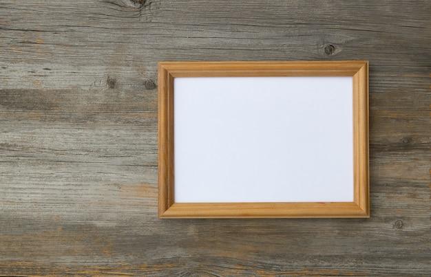 Moldura para fotos vazia na mesa de madeira clara, maquete para adicionar sua foto para copiar o espaço.
