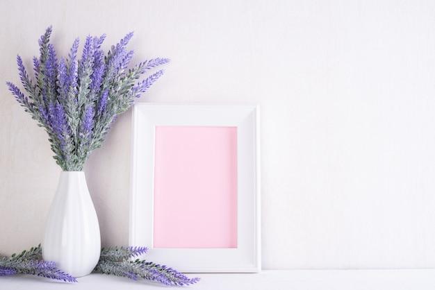 Moldura para retrato branca com a flor roxa bonita no vaso na tabela de madeira branca.