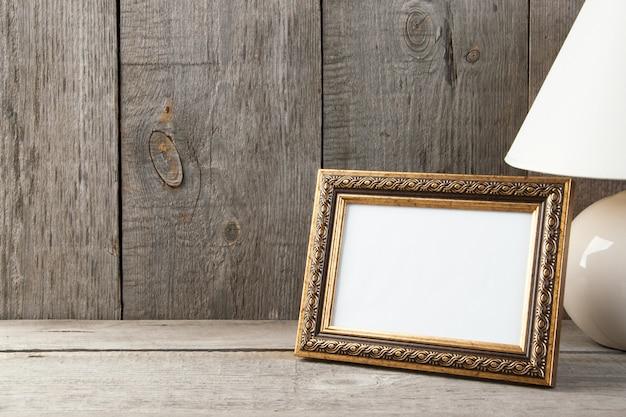 Moldura para retrato de bronze vazia no fundo de madeira.
