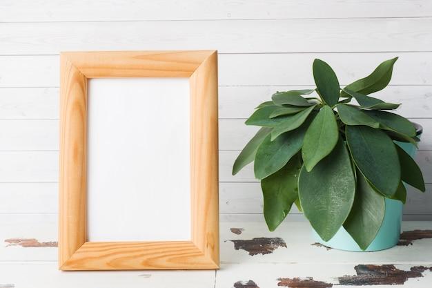 Moldura para retrato vazia de madeira e flores verdes no fundo branco.