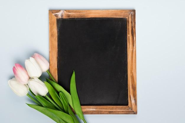 Moldura plana leiga ao lado do buquê de tulipas