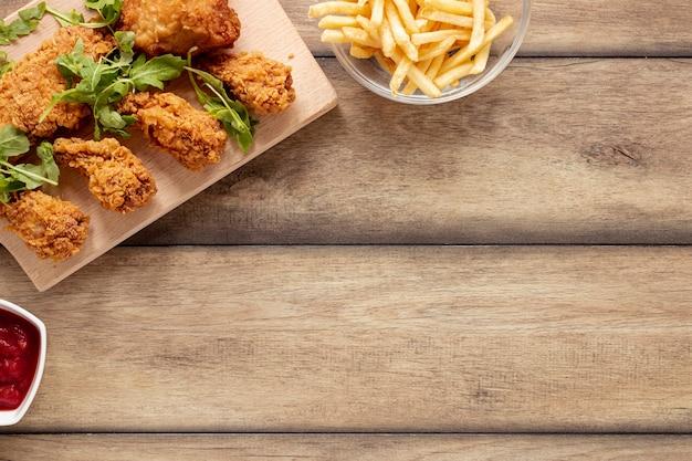 Moldura plana leiga com comida de frango e batatas fritas