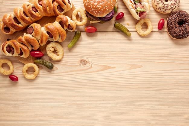 Moldura plana leiga com comida deliciosa e fundo de madeira