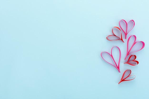 Moldura plana leiga com formas de coração e fundo azul