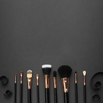 Moldura plana leiga com pincéis de maquiagem e fundo preto