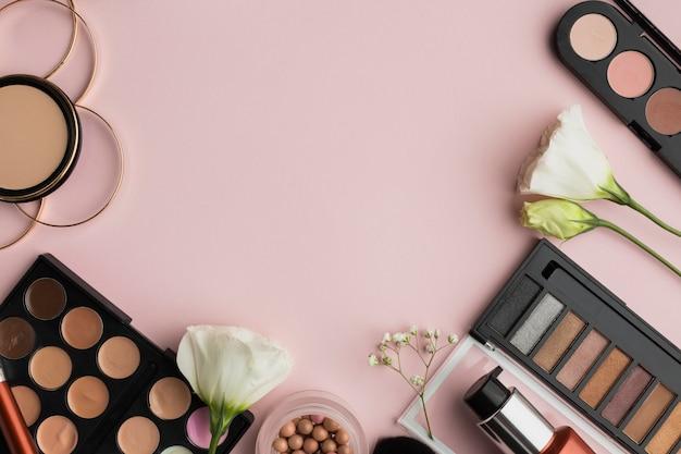 Moldura plana leiga com produtos de maquiagem e espaço para texto