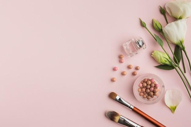 Moldura plana leiga com produtos de maquiagem e flores