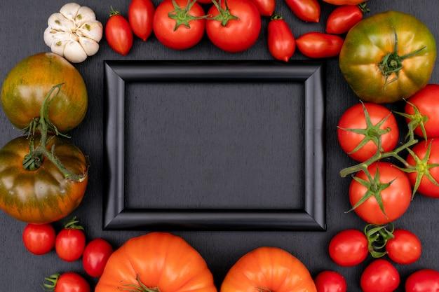 Moldura preta com espaço de cópia, rodeada por tomates vermelhos frescos, tomate cereja alho na superfície preta