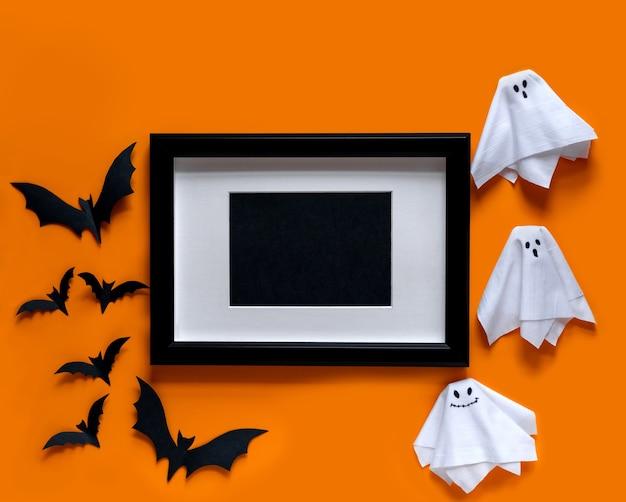 Moldura preta com morcegos e fantasmas em fundo laranja. camada plana, vista superior.