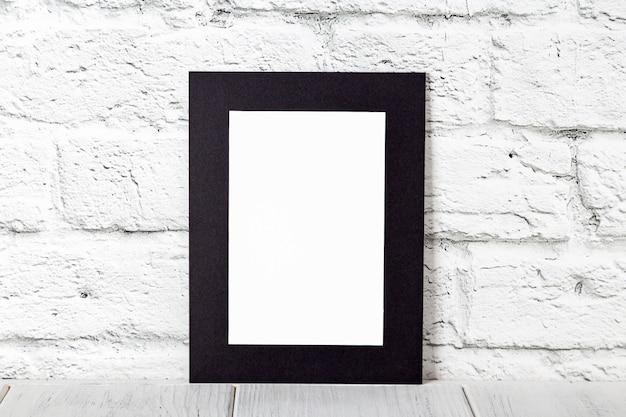 Moldura preta vertical na mesa de madeira. maquete com espaço para texto