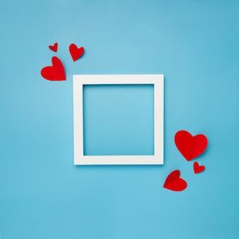 Moldura quadrada branca sobre fundo azul com corações de papel