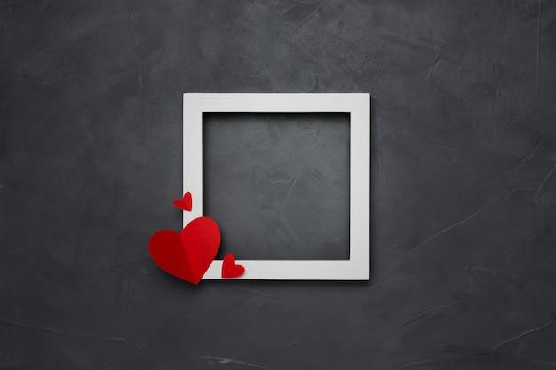 Moldura quadrada branca vazia com corações no plano de fundo texturizado cinza com copyspace