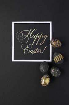 Moldura quadrada com ovos de páscoa pretos com padrão ouro sobre fundo preto. páscoa luxuosa
