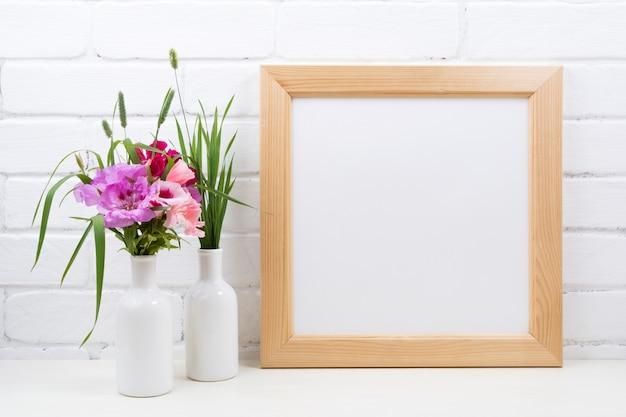 Moldura quadrada de madeira com flores rosa godetia