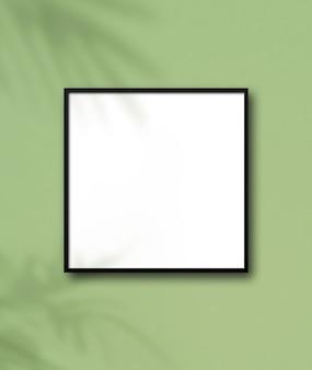 Moldura quadrada preta pendurada em uma parede verde claro