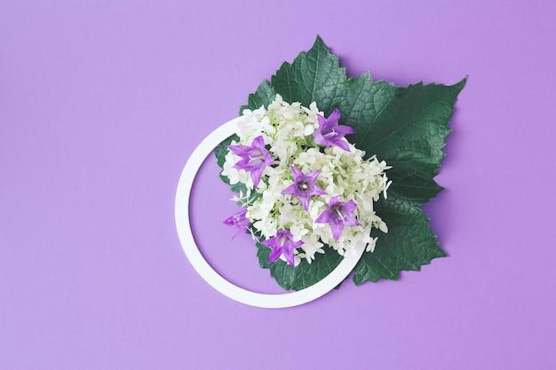 Moldura redonda branca com flores brancas e roxas e folhas verdes sobre fundo lilás. postura plana. composição minimalista de verão e primavera