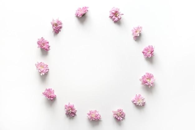 Moldura redonda com botão de flores rosa isolado no fundo branco. camada plana, vista superior.